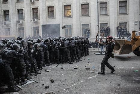 Участник акции сторонников евроинтеграции Украины перед строем сотрудников правоохранительных органов во время беспорядков возле здания Администрации президента Украины на Банковой улице в Киеве.
