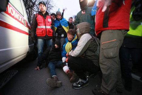 Медики оказывают помощь раненому в ходе беспорядков возле здания Администрации президента Украины на Банковой улице в Киеве.