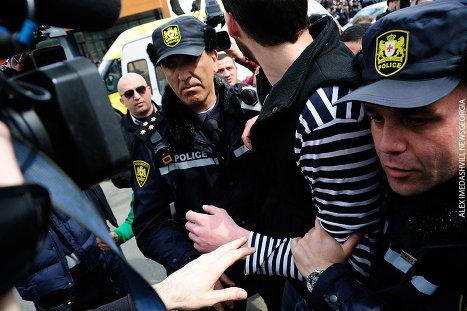полиция задерживает участника акции