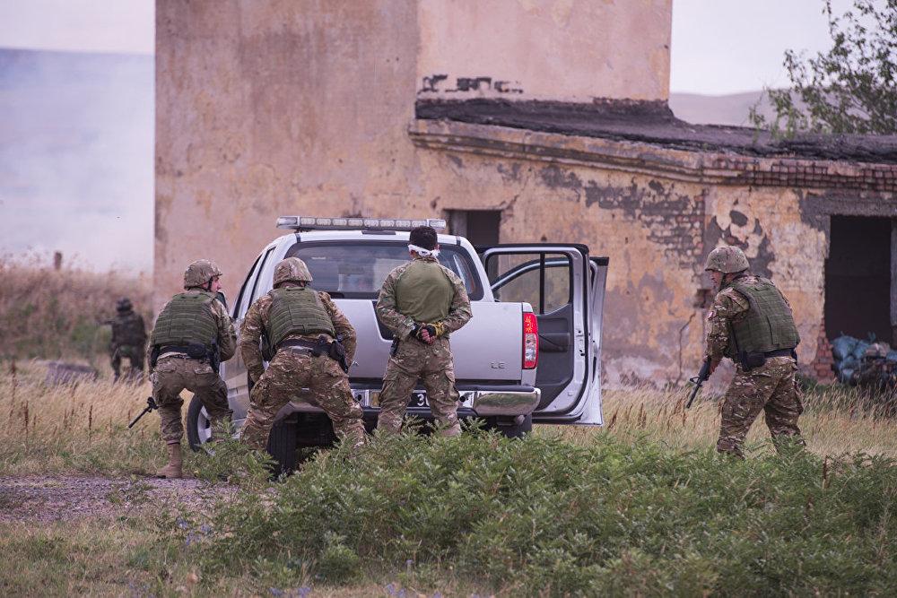В ходе учений несколько боевиков были взяты в плен. Затем военнослужащие продемонстрировали, как автомобильный конвой вывозит задержанных с поля боя.