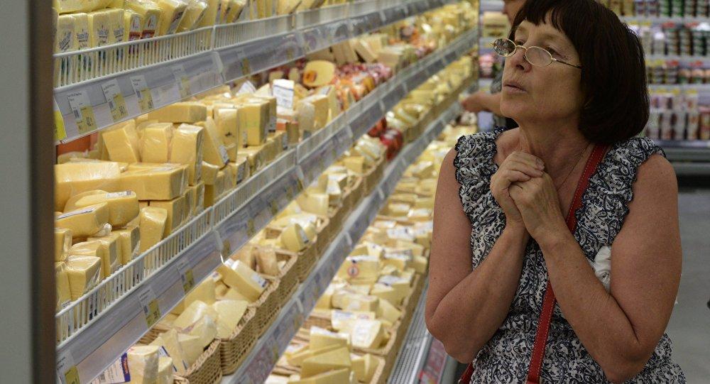 Женщина у прилавка с сырами в гипермаркете.