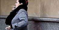 Женщина курит на одной из улиц Москвы.