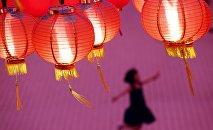 Ребенок играет под фонарями в храме в Куала-Лумпур (Малайзия), украшенном к празднованию китайского Нового года.