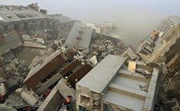 Спасатели работают на месте разрушенного землетрясением 17-этажного здания в Тайнане, Тайвань.