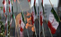 Житель Ирана выглядывает из окна автобуса в Тегеране во время празднования Дня Исламской революции.