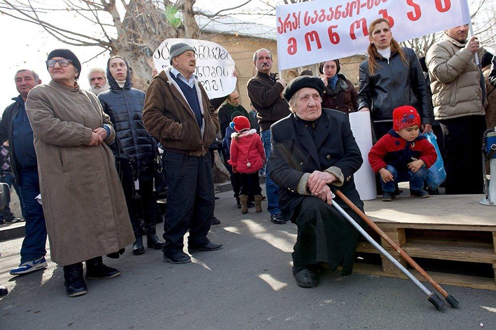 Участники акции у президентского дворца в Тбилиси слушают выступление одного из своих единомышленников.