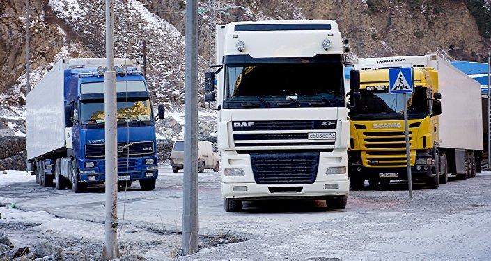 Белый трейлер водителя Арсения пересекает грузинскую границу, следуя по Военно-Грузинской дороге.
