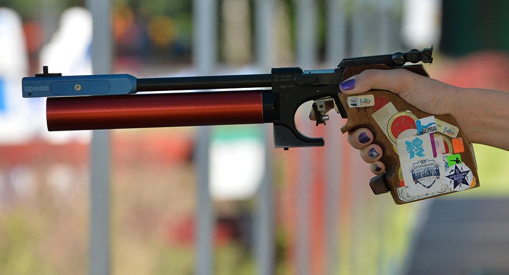 Пневматический пистолет в руке спортсменки