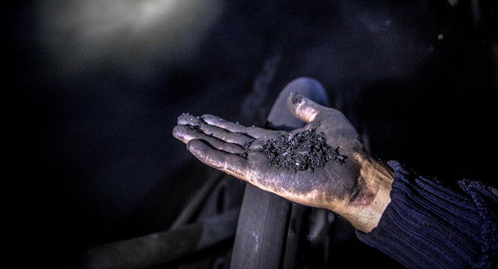 Шахтер показывает уголь на шахте