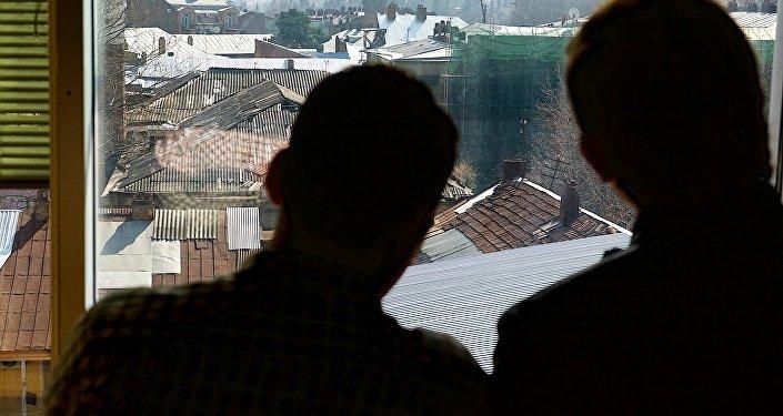 Двое мужчин смотрят в окно на город