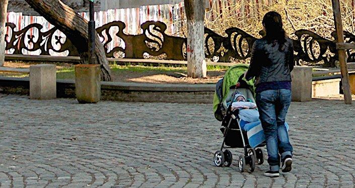Женщина с ребенком гуляют в парке в центре грузинской столицы