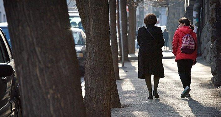 Женщина идет с девочкой по центру Тбилиси