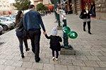 Родители с ребенком гуляют по улице
