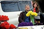 Мужчина, торгующий цветами на цветочном рынке, вместе со своей дочерью радуется празднику 8 марта.