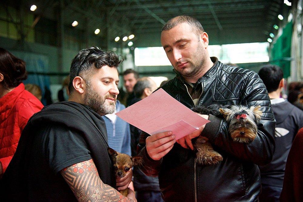 Участники Международной выставки собак в Тбилиси со своим питомцем и полученной наградой.