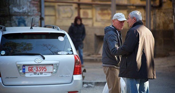 Люди беседуют на улице на площади Гудиашвили