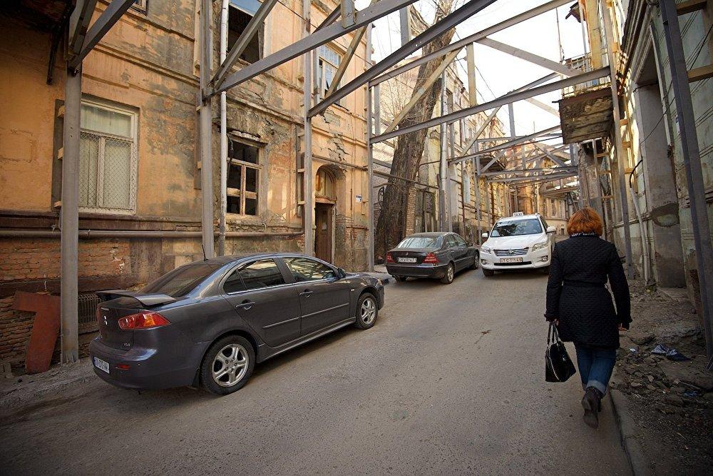 Женщина поднимается по улице Ахоспирели к площади Гудиашвили. Настречу ей едет машина - улица открыта для движения легкового транспорта.