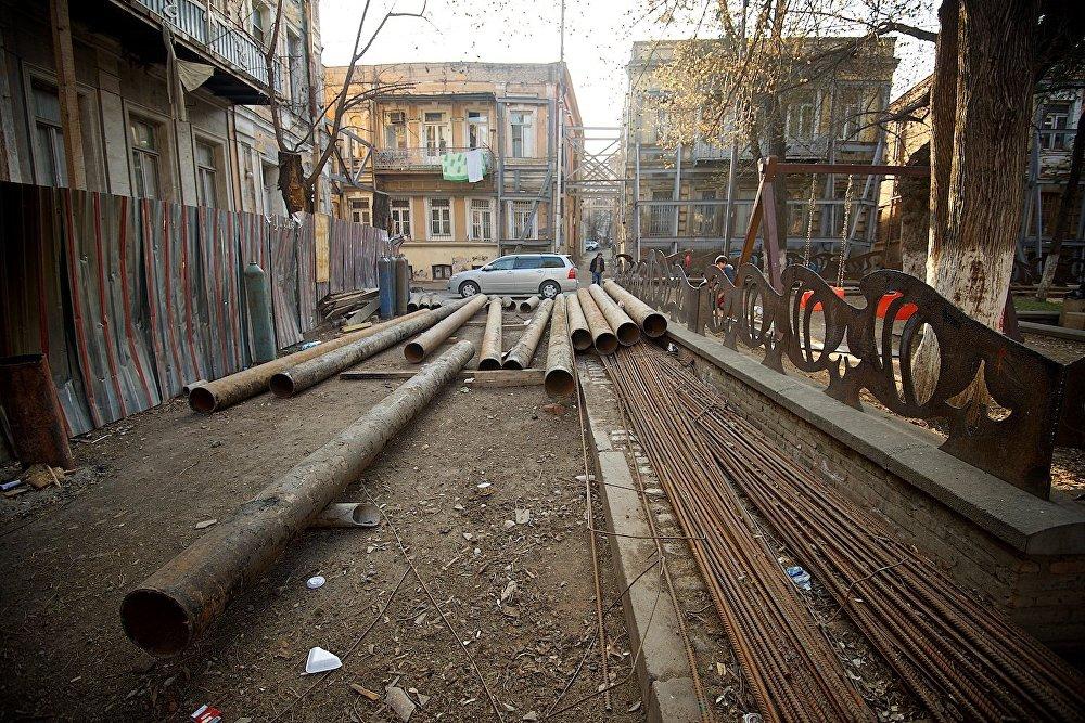 Железные конструкции, приготовленные для восстановительных работ на площади Гудиашвили. Тем временем справа в парке на площадке играют дети. Застанут ли они эти дома, когда вырастут?