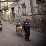 Мужчина, собирающий старые и ненужные вещи, спускается по улице Ахоспирели.