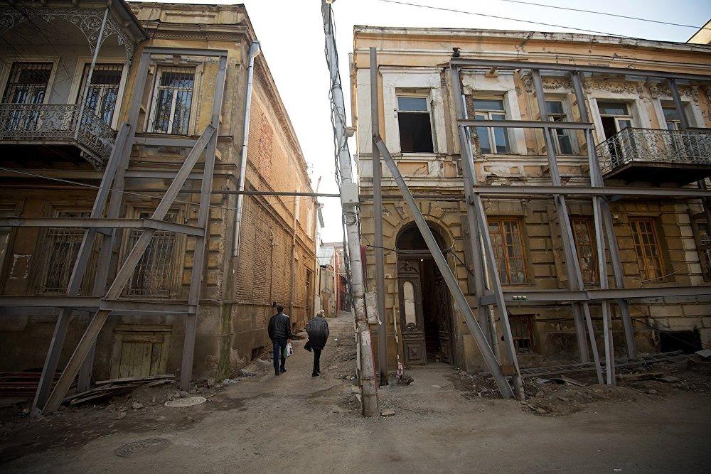 Местные жители проходят между двумя старыми домами на площади Гудиашвили.