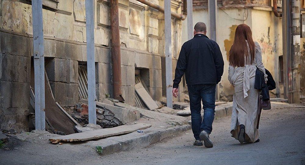 Мужчина и женщина идут по старому Тбилиси