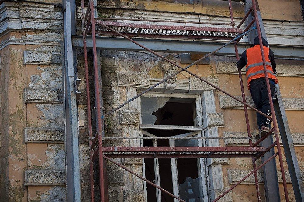 Рабочий во время восстановительных работ в одном из домов на площади Гудиашвили. Судя по всему, эта часть дома покинута.