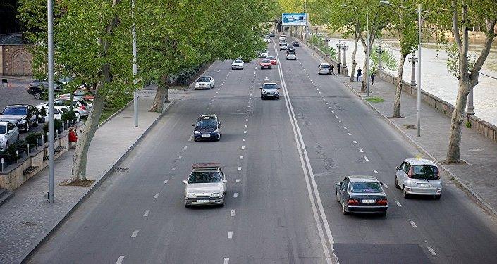Машины едут по центральной дороге вдоль набережной Тбилиси