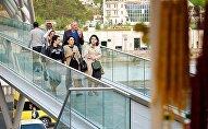 Прохожие идут по мосту Мира в центре грузинской столицы