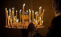 Верующая ставит свечу у иконы в кафедральном соборе Светицховели