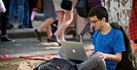 Молодой человек работает за ноутбуком, сидя на земле в парке. Хипстерский рынок
