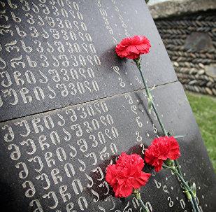 Цветы на надгробной плите на одном из братских кладбищ погибших в годы Второй мировой войны