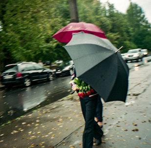 Люди под зонтом во время дождя