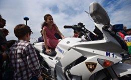 Дети фотографируются на полицейском мотоцикле во время празднования Дня Независимости Грузии