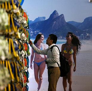 Мужчина выбирает тапочки с олимпийской символикой в открывшемся в Рио-де-Жанейро перед Олимпиадой магазине Megastore Rio 2016.
