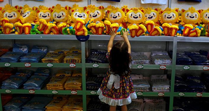 Девочка пытается достать с полки Megastore Rio 2016 в Рио-де-Жанейро куклу с олимпийской символикой.