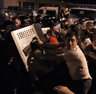Протестующие во время столкновения с полицейскими на улице близ захваченного в Ереване здания полка патрульно-постовой службы.