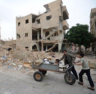 Жители населенного пункта в Сирии, где здания пострадали в результате обстрелов