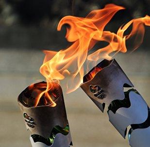 Жители Бразилии передают друг другу олимпийский огонь, зажигая факелы, в ходе эстафеты Олимпийского огня. Парк Независимости в Сан-Паулу, Бразилия.