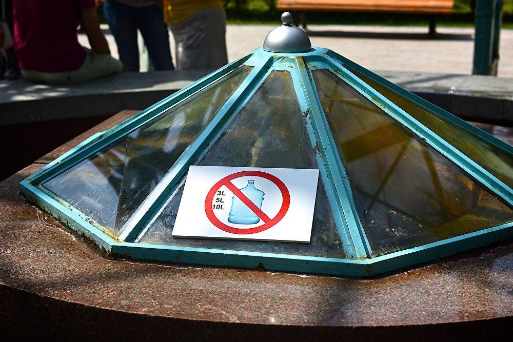 Предупреждающая надпись на листе бумаги у источника с минеральной водой Боржоми в городском парке.