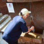 Сотрудница Боржомского парка наполняет для посетителей пластиковые бутылки минеральной водой из действующего там источника.