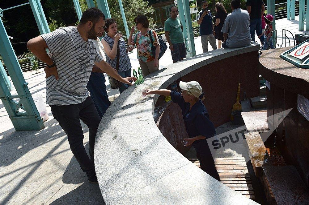 Сотрудница Боржомского парка наполняет стаканы и бутылки посетителей минеральной водой из подземного источника