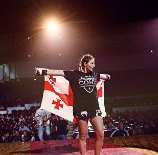 Лиана Джоджуа держит грузинский флаг после соревнований по ММА