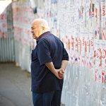 Житель Тбилиси проходит мимо забора, на котором наклеены предвыборные плакаты