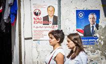 Женщины проходят мимо здания, на стене которого наклеены предвыборные плакаты