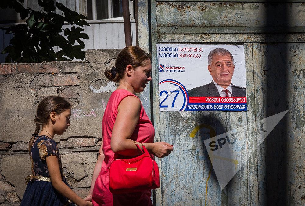 Женщина с ребенком идет мимо здания, на стене которого наклеены предвыборные плакаты