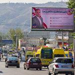 Один из предвыборных плакатов, размещенный над оживленной трассой в столице Грузии