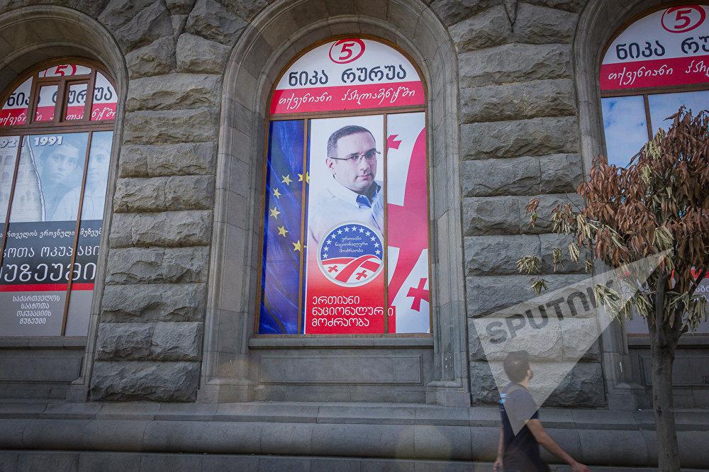 Предвыборный плакат одной из оппозиционных партий, размещенный в оконном проеме в здании в центре столицы Грузии.
