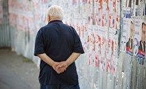 Мужчина проходит мимо предвыборных плакатов