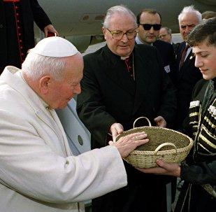 Девочка и мальчик, одетые в традиционные одежды, преподнесли на блюде Иоанну Павлу II грузинскую землю для поклонения. Из-за плохого самочувствия понтифик не смог склониться к ней сам, как это делал по традиции.