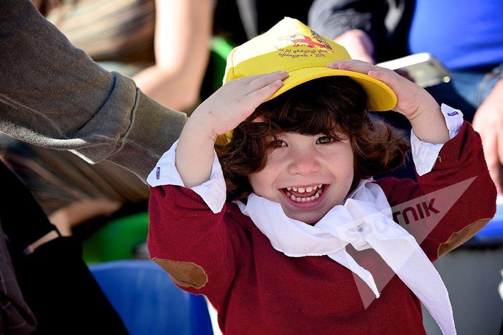 Девочка во время католической мессы Папы Римского Франциска на стадионе имени Михаила Месхи